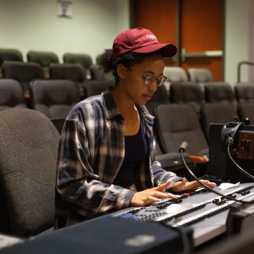 Students working with soundboard in chapel building