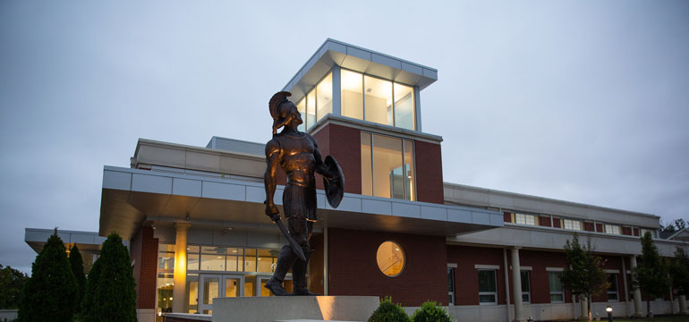 spartan statue in front of gym building
