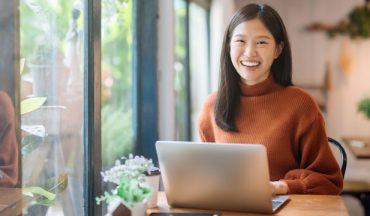 Smiling adult woman in orange sweater with laptop